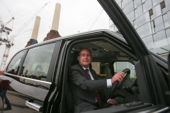 Chris Gubbey, pdg de la London EV Company, pose dans le nouveau TX eCity électrique, devant l'ancienne centrale électrique Battersea à Londres. (AFP)