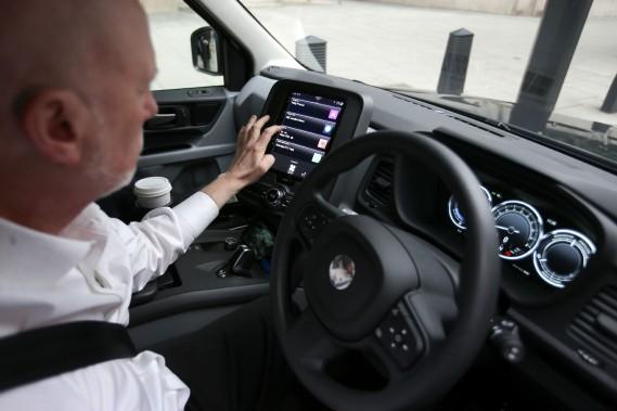 Peter Powell, âgé de 61 ans et chauffeur de taxi à Londres depuis 21 ans, accepte une course relayée sur l'écran tactile de son ordinateur de bord.Il aime le nouveau TX eCity, mais il dit que les chauffeurs plus âgés n'aiment pas le changement, en général. (AFP)