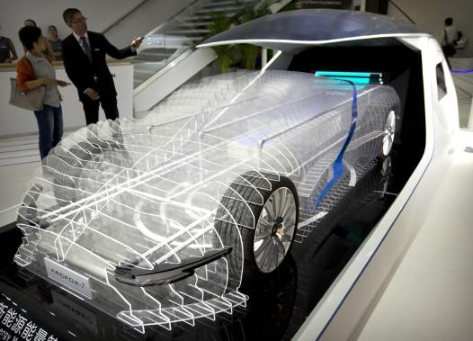 Un employé parle à un visiteur devant un modèle représentant les composantes intérieures du prototype de voiture sport électrique Arcfox-7 lors du Salon de l'auto de Pékin le 26 avril 2016. (AP)