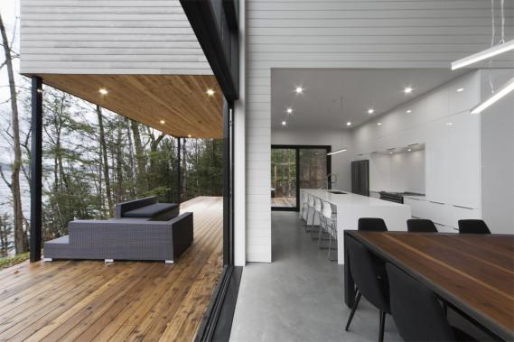 Une large porte pliante à la base du mur-rideau permet d'agrandir la salle à manger et de recevoir de très grandes tablées aux beaux jours. «On a fait un plateau pour asseoir le rez-de-jardin, car il y a un dénivelé imposant. C'était important d'avoir des espaces extérieurs connectés avec le chalet et le terrain», dit l'architecte. La symétrie entre l'intérieur et l'extérieur forme une belle perspective. (PHOTO STEVE MONTPETIT FOURNIE PAR ATELIER BOOM TOWN)