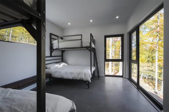Un dortoir s'ajoute aux quatre chambres de la résidence et la capacité de couchage peut aller jusqu'à 16 personnes. Quand les propriétaires l'ont fait construire, ils souhaitaient profiter de la maison, mais aussi la louer. Plusieurs familles peuvent se retrouver ici, et c'est très festif pour les enfants d'être tous regroupés dans ce même espace pour dormir. (PHOTO STEVE MONTPETIT FOURNIE PAR ATELIER BOOM TOWN)