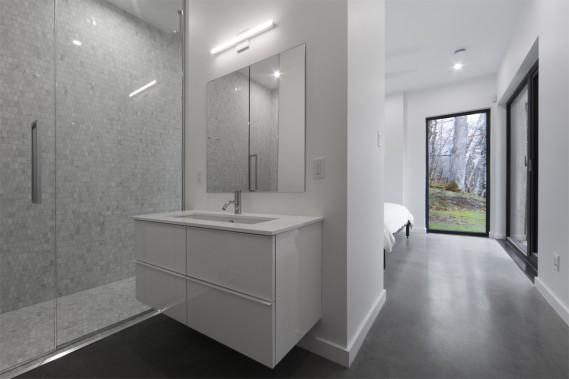 Le plancher de béton radiant dans toute la maison maximise le confort, notamment dans les salles de bains. La douche de celle-ci est revêtue de mosaïque de marbre (Ciot), dont la noblesse fait écho à celle de tous les matériaux qui habitent la demeure. Meuble-lavabo: IKEA; comptoir en quartz: Ciot; robinetterie Rubi et céramique Ramacieri Soligo. (PHOTO STEVE MONTPETIT FOURNIE PAR ATELIER BOOM TOWN)