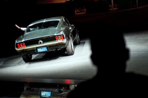 Sean Kiernan, qui a hérité de son grand-père la Mustang fastback conduite par Steve McQueen durant le tournage du film Bullitt, salue l'assistance, avant l'arrivée sur scène de la Bullitt 2019. (The Flint Journal-MLive.com via AP)