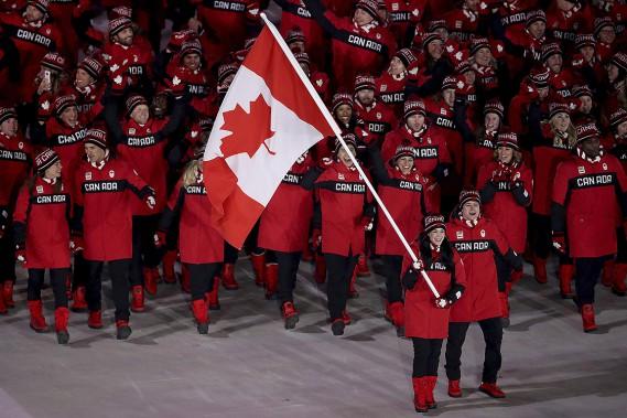 Les danseurs sur glace et porte-drapeaux canadiens Tessa Virtue et Scott Moir, devant la délégation du Canada. Ces deux athlètes ont ainsi amorcé leur dernière aventure olympique. (Sean Haffey, AP)