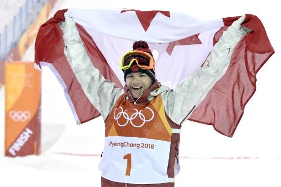 Mikaël Kingsbury brandit le drapeau canadien après avoir remportéle seul titre qui manquait encore à son palmarès: l'or olympique. (Photo Bernard Brault, La Presse)