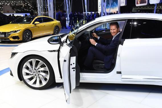 Herbert Diess, le patron de la marque Volkswagen, photographié au volant de l'Arteon(en configuration européenne), lors de son dévoilement mondial au Salon de l'auto de Genève le 17 mars 2017.<br /><br /> (photo AFP)