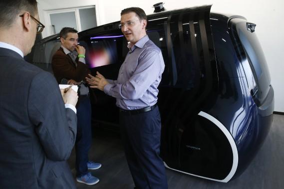 Le chef de la direction numérique du Groupe Volkswagen, Johann Jungwirth, parle avec des journalistes devant le prototype de minibus sans conducteur Sedric, mardi matin, lors d'un événement de presse Volkswagen. (AP)