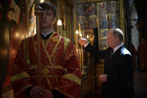Vladimir Poutine allume un lampion après son déplacement en limousine russe Aurus Kortezh et son investiture comme président de la Russie. (Photo Agence Spoutnik, via AFP)