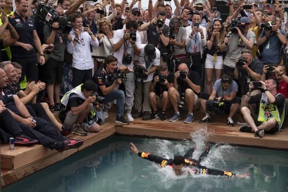 Le pilote de F1 l'Australien Daniel Ricciardo plonge dans une piscine tout habillé après sa victoire dimanche au GP de Monaco. (AP)