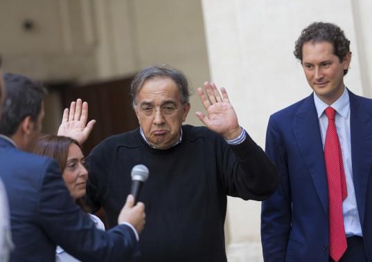 Dans cette photo prise le 25 juillet 2014, le premier ministre d'Italie Matteo Renzi (de dos, à g.) passe le micro d'un journaliste à Sergio Marchionne (au centre), qui fait semblant de ne pas vouloir répondre. Le président du conseil de Fiat, John Elkann, observe la scène. (AP)