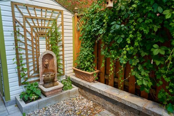 <strong>Eau bienfaisante:</strong>La fontaine renforce l'atmosphère tranquille de la cour, car le ruissellement de l'eau est très relaxant. Elle est adossée au cabanon, dont la cloison blanche est adoucie par le treillage en bois naturel et les végétaux qui l'habillent. Un lit de petites roches au sol favorise le drainage de l'eau en plus de s'harmoniser avec les tons de la pierre du sol et du muret. (Photo André Pichette, La Presse)