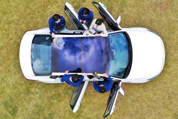 Peut-être pas encore la voiture de l'année, mais probablement la photo la plus mise en scène de l'année. Le personnel de recherche prend la pose pour cette photo autour d'un toit panoramique muni de capteurs solaires. ()