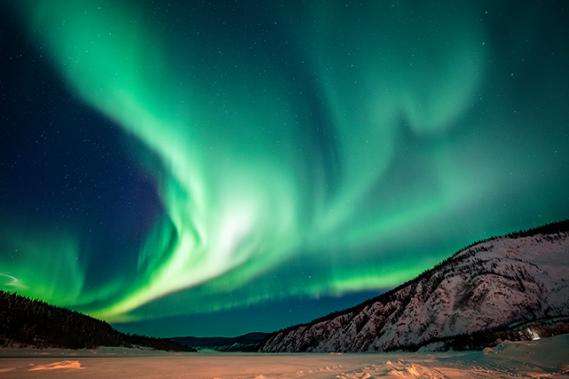 L'aurore boréale est une réaction luminescente qui se produit lorsque des particules expulsées par le soleil entrent en collision avec les atomes d'oxygène et d'azote du champ magnétique terrestre. ()