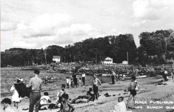 L'Église n'aimait pas trop voir ces vacanciers dénudés et oisifs, ce qui n'a pas empêché les Canadiens français de fréquenter les plages, qu'elles soient sur le bord du fleuve Saint-Laurent ou des lacs. Sur cette photo des années30, des baigneurs au lac Simon. (PHOTO FOURNIE PAR BANQ, PLAGE PUBLIQUE AU LAC SIMON ET CAMPS ARCHAMBAULT EN ARRIÈRE-FOND, [193-?]. BANQ GATINEAU, FONDS COMITÉ DES FÊTES DE CHÉNÉVILLE (P83, D109). PHOTOGRAPHE:NON IDENTIFIÉ)