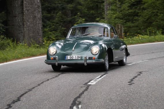 À l'époque, la genèse de cette voiture, élaborée dans les années 40, n'était pas très claire. Conçue sous la direction de Ferry Porsche, la 356 semblait dérivée assez étroitement de l'antique VW Coccinelle conçue avant la guerre par son père, le célèbre ingénieur Ferdinand Porsche. D'ailleurs, la 356 en conserve intégralement l'architecture à moteur arrière en porte-à-faux, et en substance, les trains roulants ainsi que la base du moteur à... ()