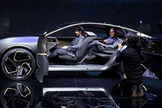 Le design du prototype Nissan IMs profite pleinement de l'espace intérieur accru de la voiture électrique. Ci-haut, le designer Alfonso Albaisa, de Nissan, montre comment le passager du milieu peut étendre ses jambes entre les deux sièges avant. (Photo Nissan)