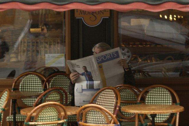 Un homme lit le journal sur une terrasse... (Archives La Presse)