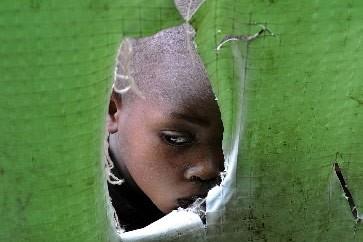 Ce garçon regarde au travers une tente qui... (Photo: AFP)
