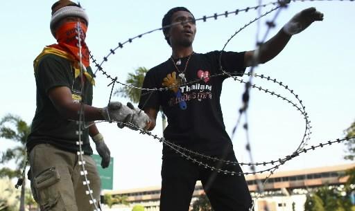 Des manifestants anti-gouvernement érigent une barrière de barbelés... (Photo: AP)
