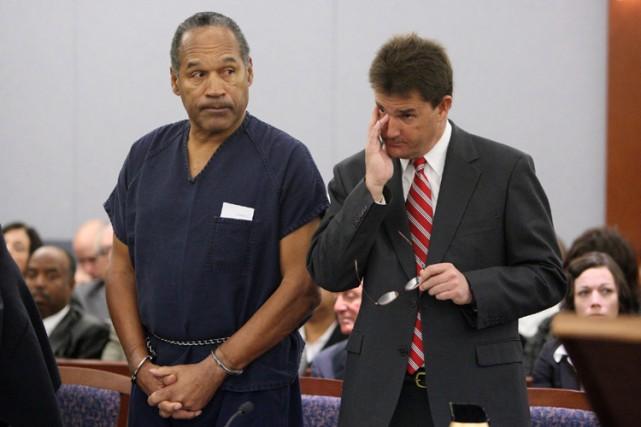 Menotté et vêtu d'un uniforme bleu de prisonnier,... (Photo: AP)
