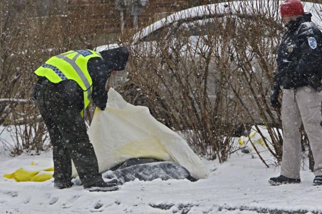 Un policier examine un des cadavres trouvés dans... (Photo: Ivanoh Demers, La Presse)