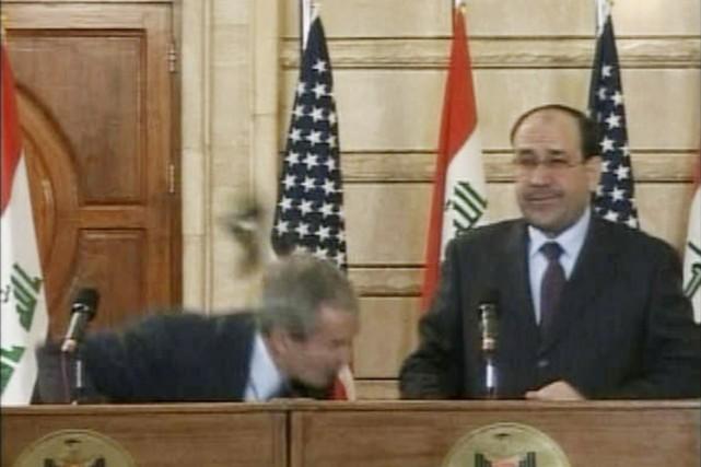 George Bush esquive habilement le premier soulier, alors... (Photo: Reuters)