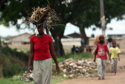 Une femme transporte du bois pour faire bouillir... (Photo: AFP)