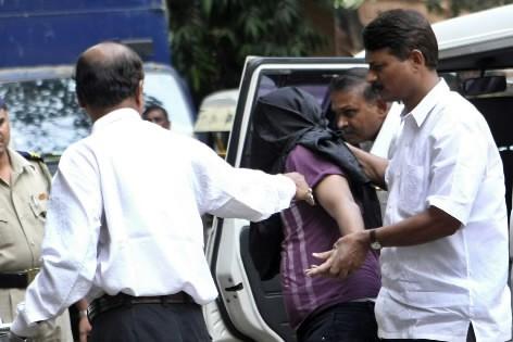 Un des suspects est escorté.... (Photo: AFP)