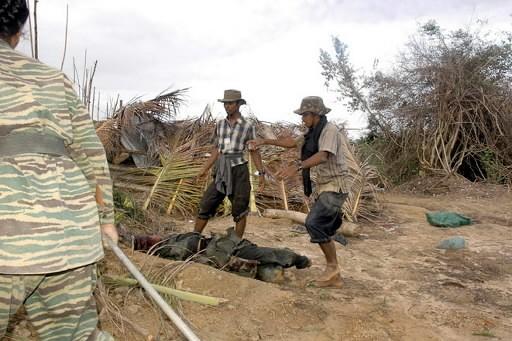 Des rebelles Tamouls regardent les corps de soldats... (Photo: AFP)
