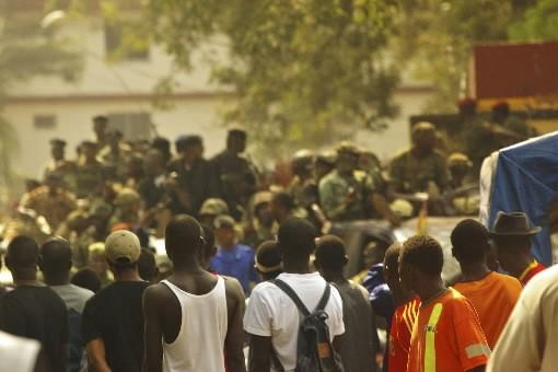 Une foule observe des soldats guinéens.... (Photo: Reuters)