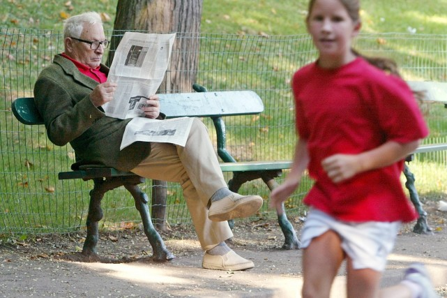 Un homme lit le journal dans un parc... (AP)
