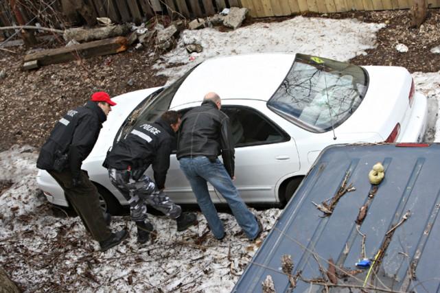 Les enquêteurs observent la voiture dans laquelle le... (Photo: Patrick Sanfaçon, La Presse)