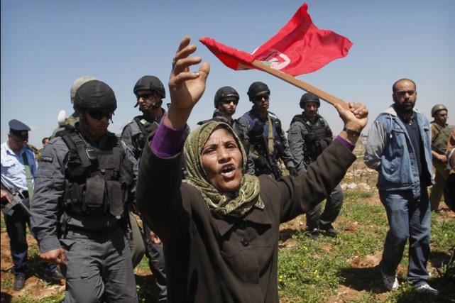 Une manifestante palestinienne est escortée par des policiers... (Photo: AP)