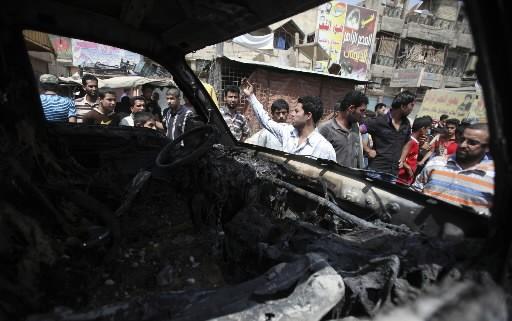 Des Irakiens s'approchent du lieu d'un des attentats.... (Photo: AP)