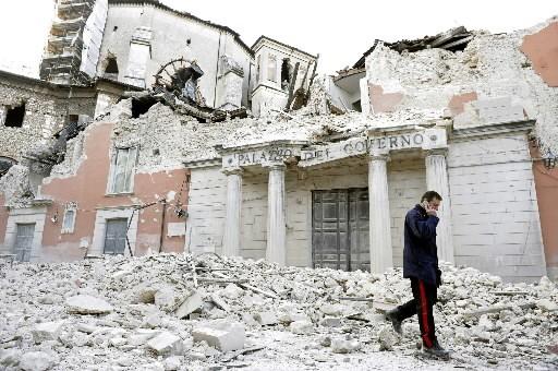 Un militaire italien passe dans le centre-ville dévasté... (Photo: Reuters)