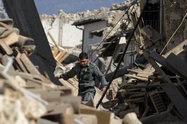 Un policier italien se promène dans les décombres.... (Photo: Reuters)