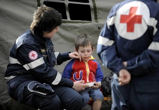 Un jeune garçon est réconforté par des secouristes... (Photo: AFP)