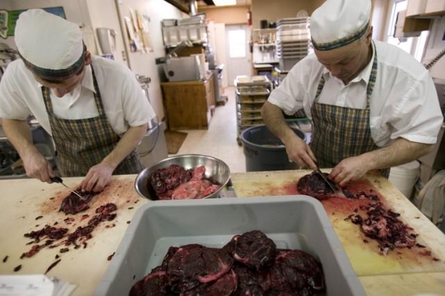 Deux cuisiniers préparent la viande phoque.... (Photo: AFP)