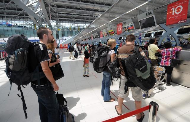 Des touristes quittant la Thaïlande attendent pour s'enregistrer... (Photo: AFP)