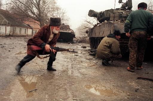 Un volontaire tchéchène prend position derrière un tank... (Photo: archives AFP)