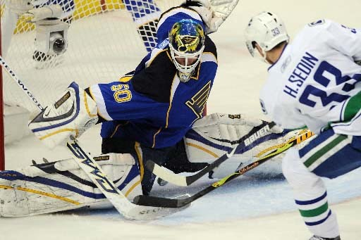 Henrik Sedin met le gardien des Blues à... (Photo Bill Boyce AP)