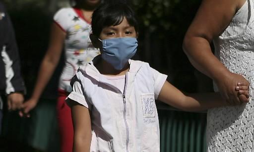 Une enfant porte un masque alors que Mexico... (Photo: Reuters)