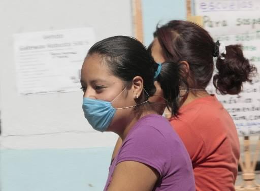 Deux femmes portant un masque passent devant une... (Photo: Reuters)