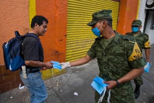 Des membres de l'armée américaine distribuent des masquent... (Photo: AFP)