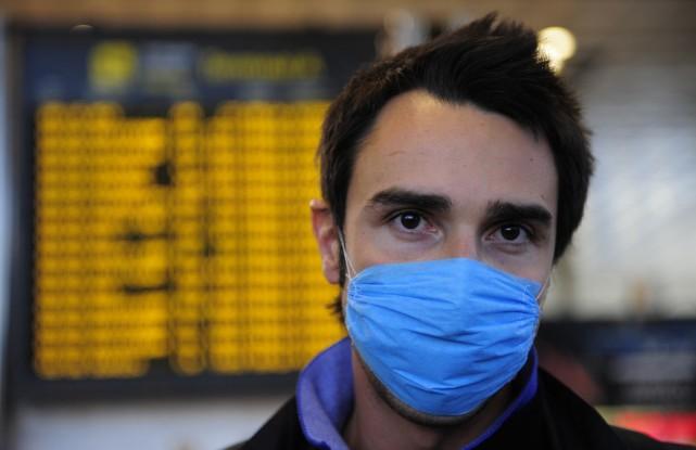 Un voyageur attend avec un masque dans un... (Photo: AP)
