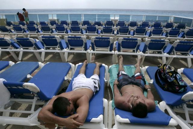 Quelques touristes prennent un bain de soleil sur... (Photo: AP)