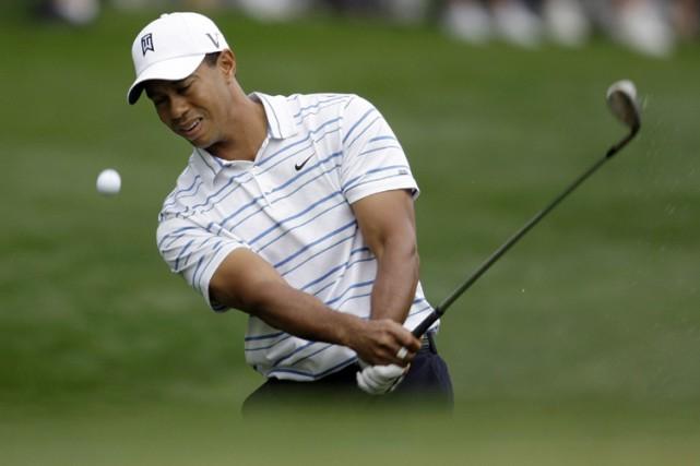 Tiger Woods effectue un coup d'approche aux abords... (Photo: AP)