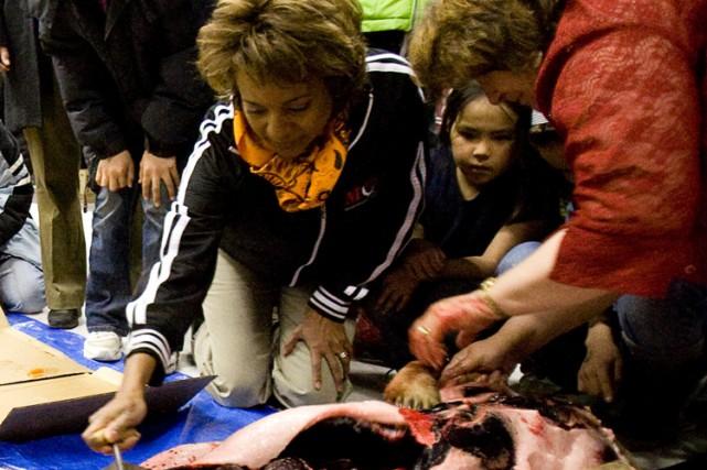 Michaëlle Jean découpe un phoque lors d'un festin... (Photo: PC)
