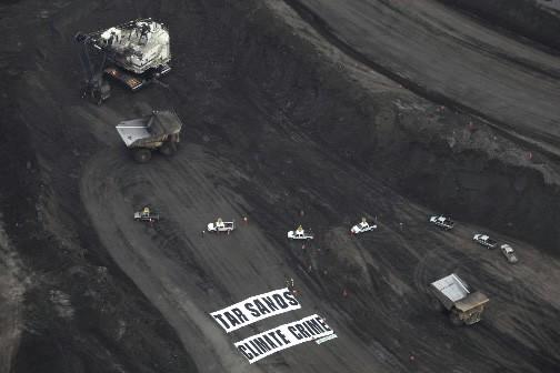 Les militants de Greenpeace déploient une bannière et... (Photo Reuters)