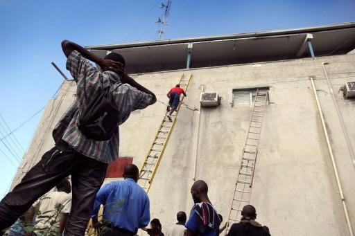 Des hommes tentent de secourir des victimes prisonnières... (Photo: AFP)